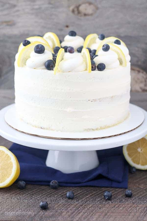 A shot of a while cake on a white cake plate. The cake is garnishes with whipped cream, lemon slices and blueberries