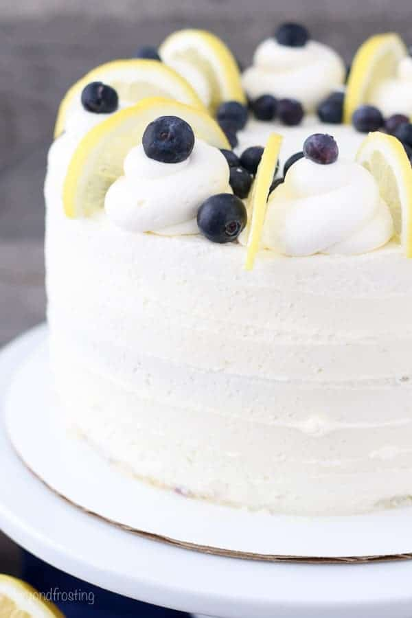 A close up shot of a layer cake topped with lemon slices and blueberrues