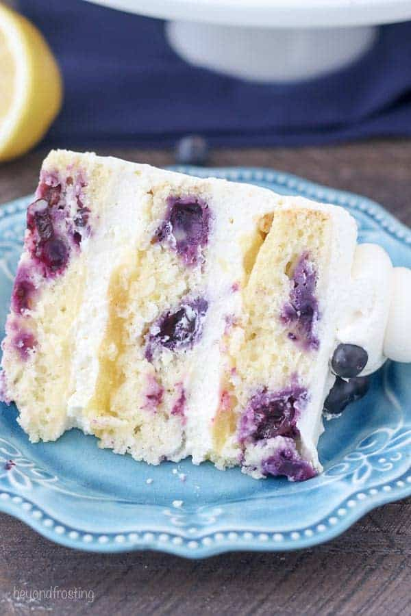 A close up shot of a lemon blueberry cake on a teal cake plate