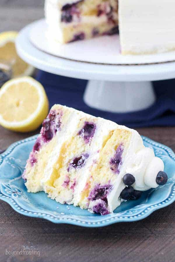 A slice of lemon cake with blueberries on a teal plate and a cake stand in the background