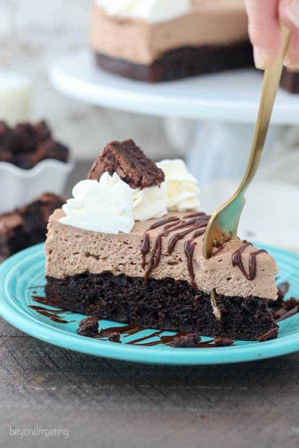 A brownie bottom chocolate cheesecake with a big gold fork digging in. It's garnished with a chocolate drizzle, whipped cream and a brownie on top.