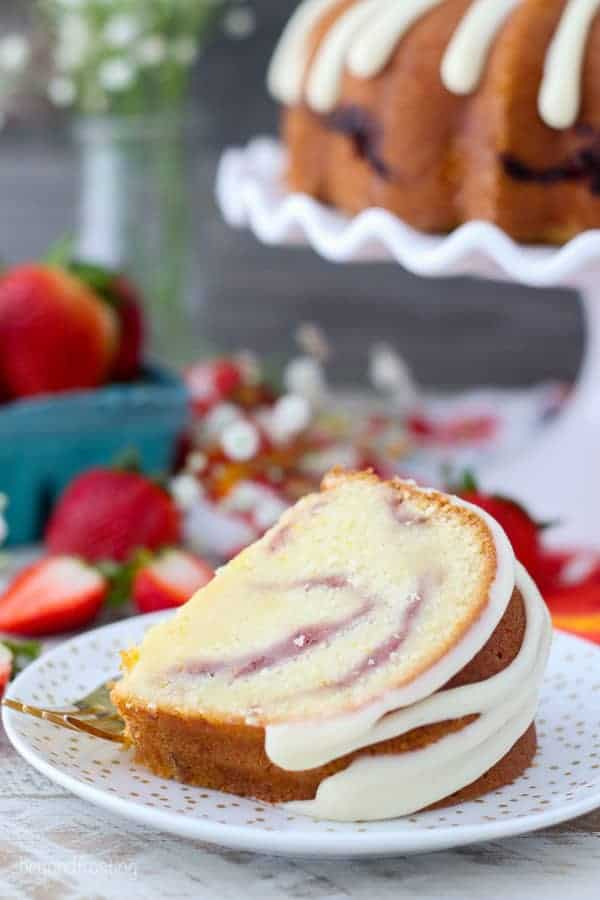 A slice of pound cake with a cream cheese glaze laying on a gold polka dot plate..