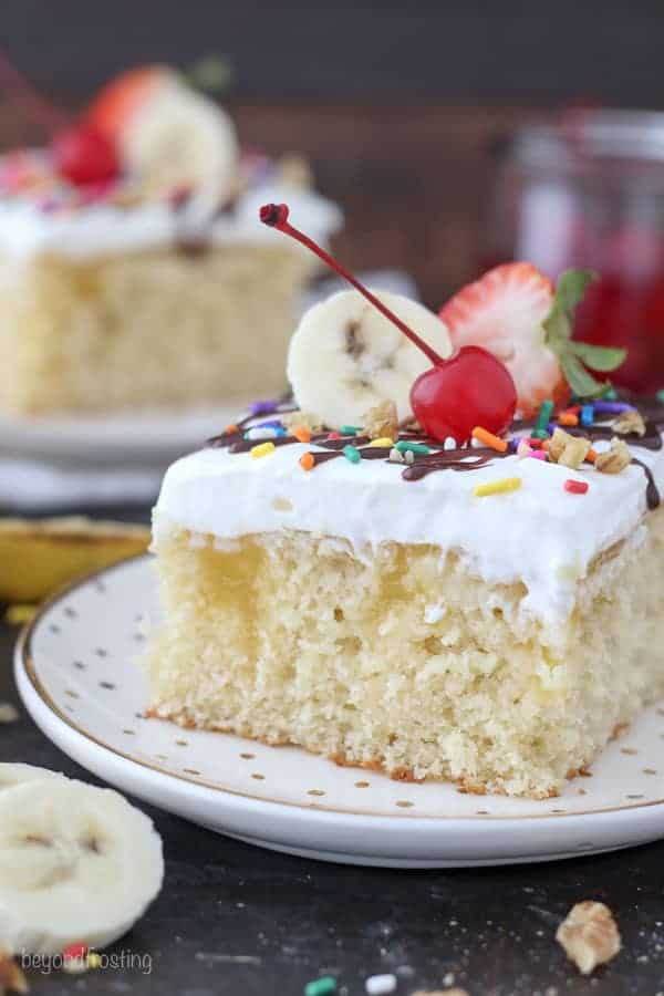 A slice of banana split cake on a gold polka dot plate. The vanilla cake is filled with a banana pudding and topped with sundae toppings