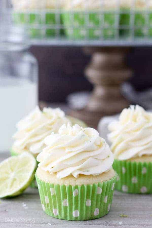 A group of 3 cupcakes with green polka dot wrapper stacked together with a lime wedge in the background