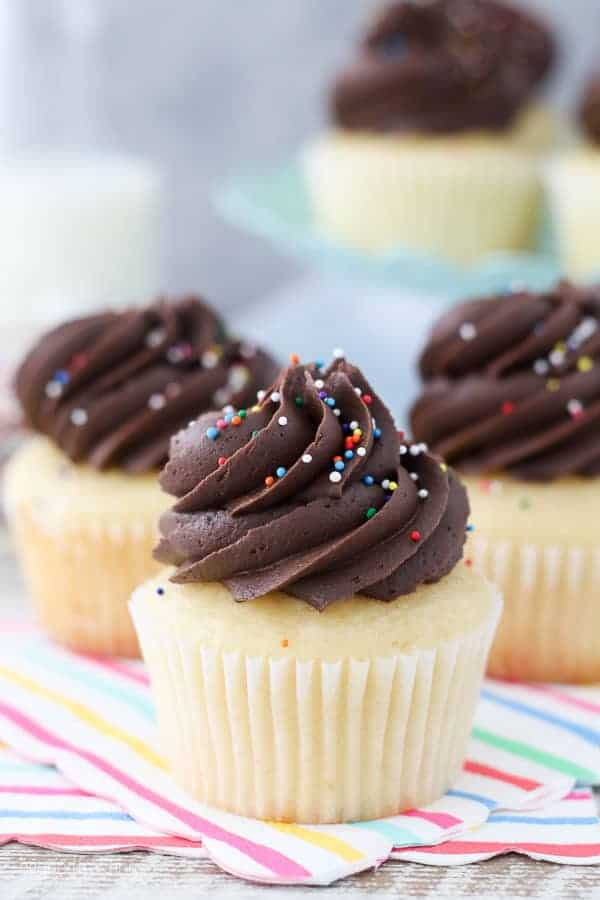 A close up shot of a perfect yellow cupcake with a big swirl of chocolate frosting and sprinkles