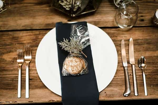 A navy blue napkin with homemade cookie favors and a juniper branch © Kimberly Kay Photography