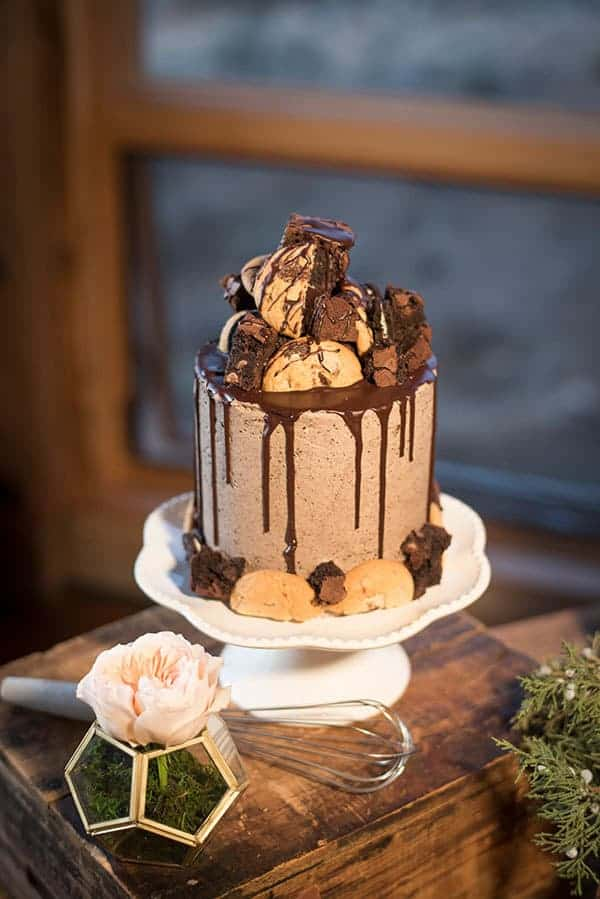 A tall cake with Oreo frosting covered in cookies, brownies and Oreos