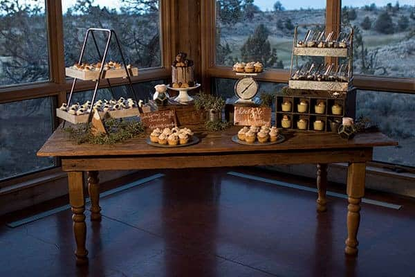 A rustic dessert table for a barn-themed wedding features pieces using varying heights, wooden boxes and cake stands at Brasada Ranch in Powell Butte Oregon