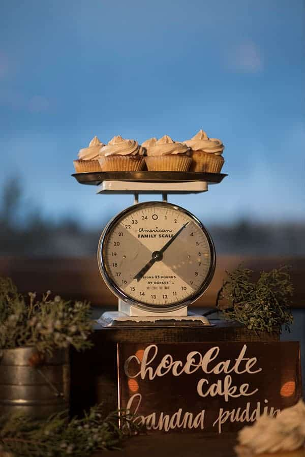 A vintage scale with a rustic metal plate and cupcakes on top were the centerpiece for this rustic dessert table