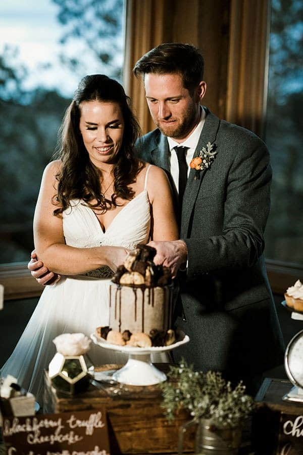 Bride and Groom cut into a Brookie Cake for their rustic bar wedding © Kimberly Kay Photography