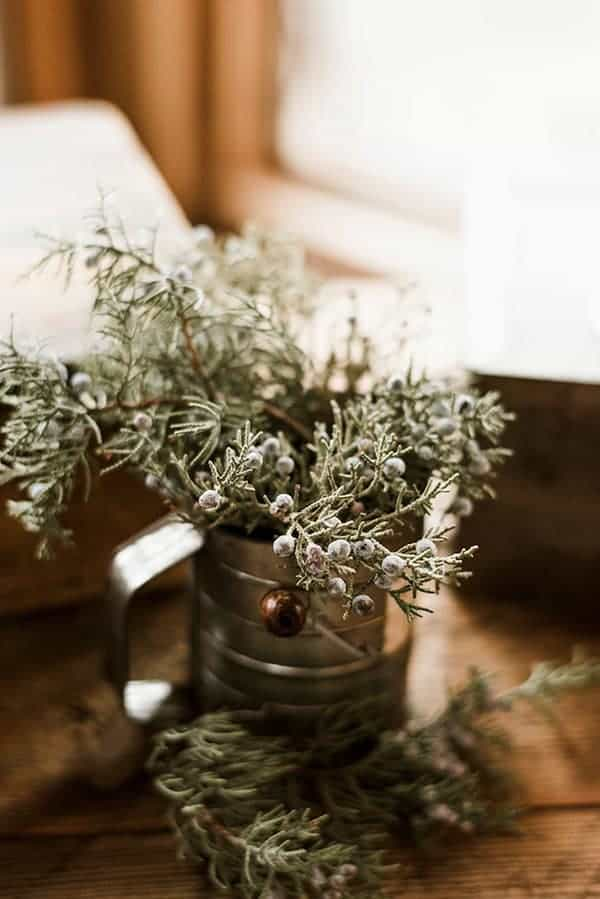 A rustic flour sifter filled with Juniper branches for a dessert table