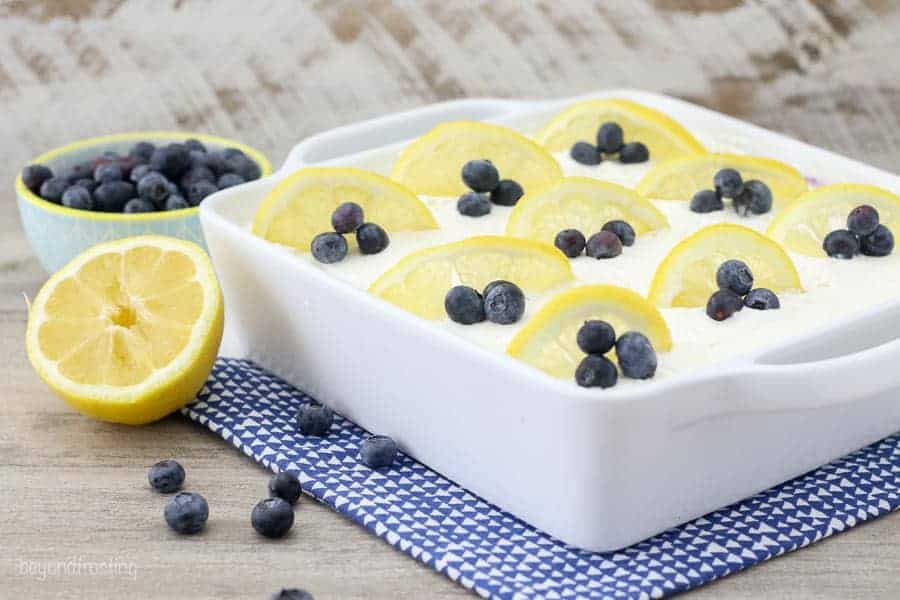 A white square dish filled with a dessert, whipped cream on top and garnished with blueberries and lemon slices.