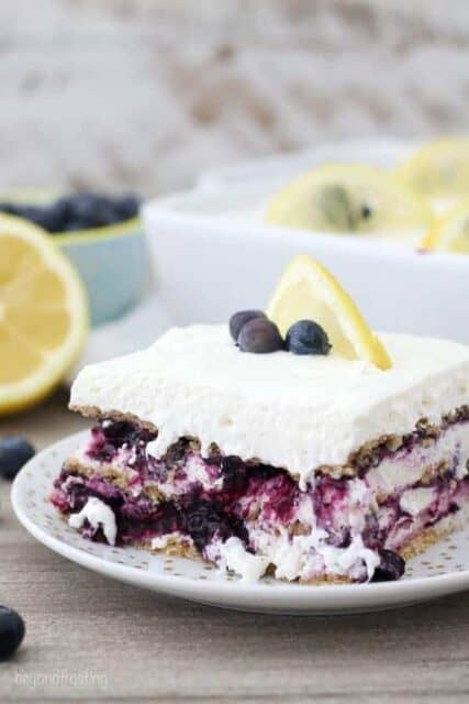A mouthwatering layered icebox cake with blueberries and a lemon wedge on top.