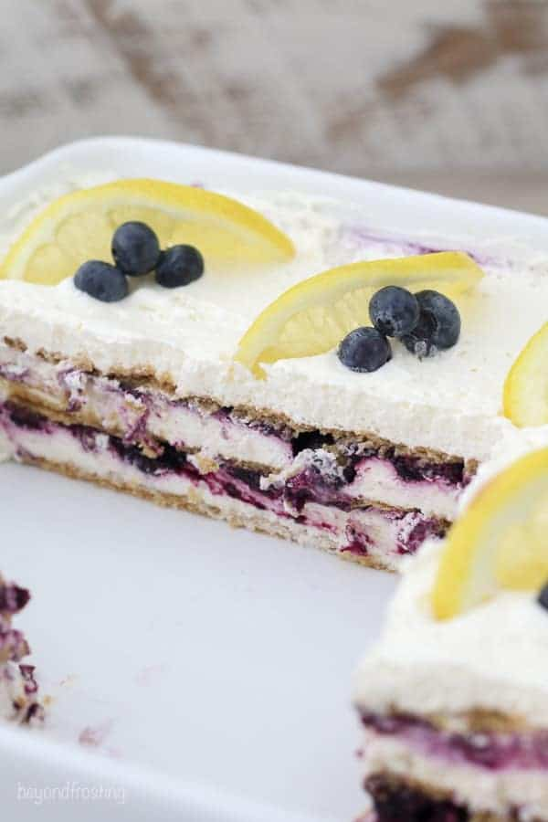 A picture of a white dish with a dessert lasagna inside, layers of graham crackers, blueberries and lemon slices.