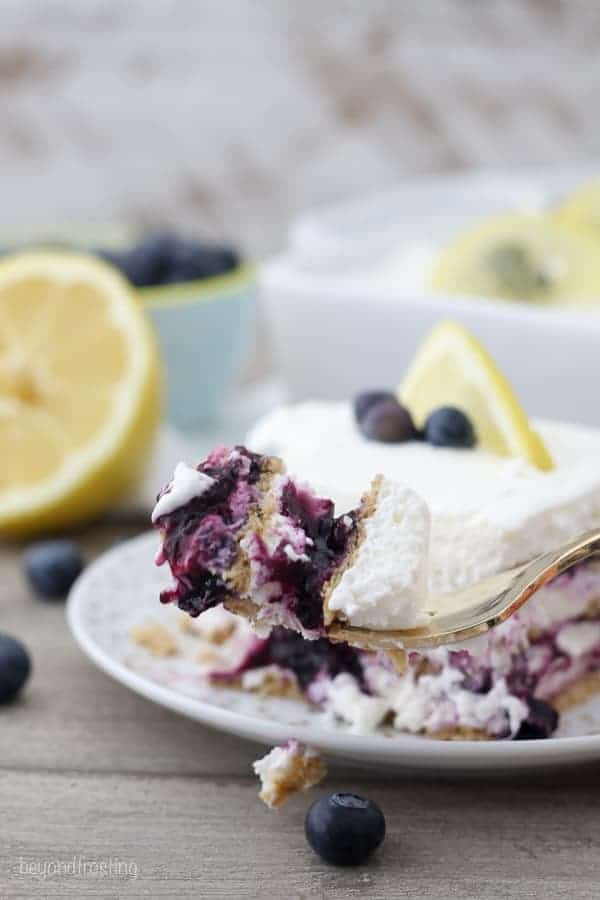 A fork loaded with a bite of this layered blueberry lemon icebox cake