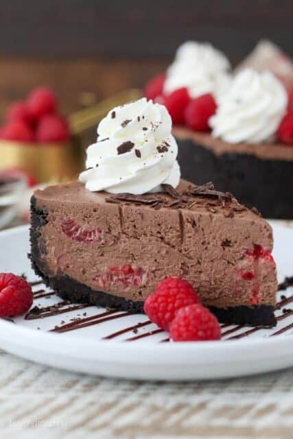 A big slice of chocolate cheesecake on a white plate drizzled with chocolate, whipped cream and garnished with raspberries