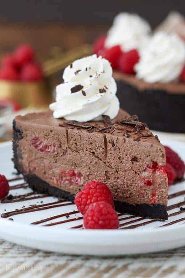 A big slice of chocolate cheesecake on a white plate drizzled with chocolate and garnished with raspberries