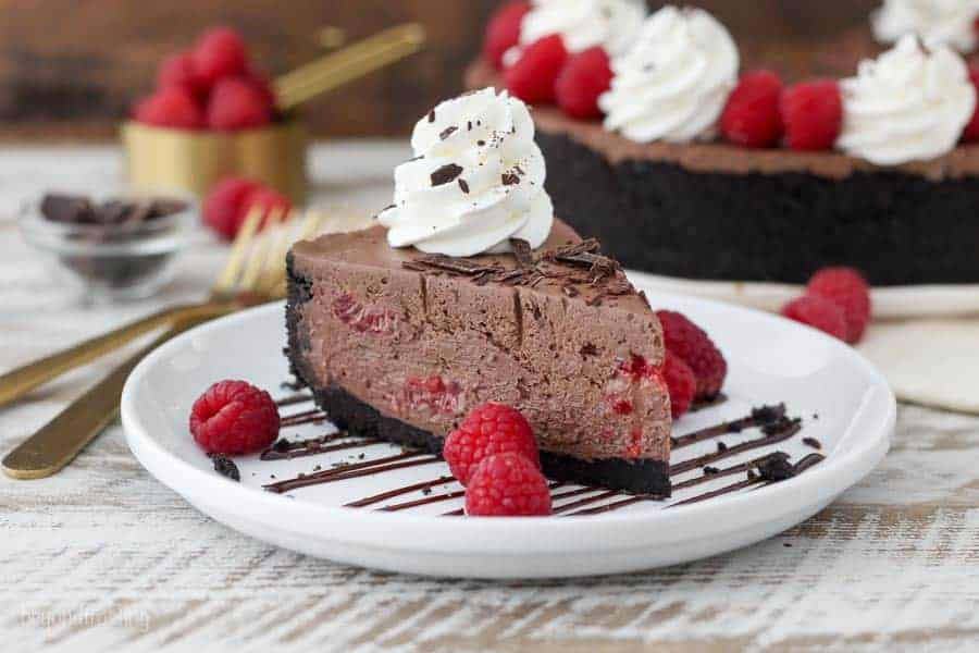 A large chocolate cheesecake garnished with whipped cream chopped chocolate and raspberries.