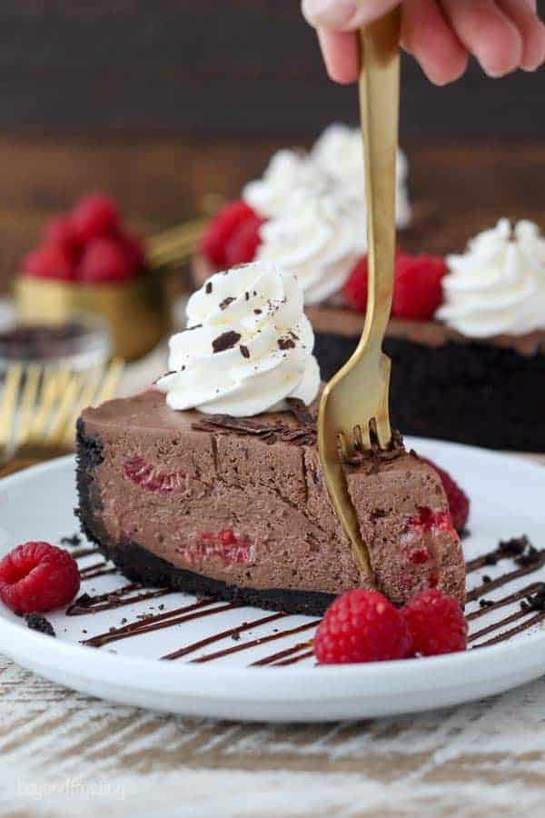 A gold fork sinking into a slice of chocolate cheesecake that is loaded with raspberries