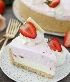 A slice of mousse cake with two layers, the bottom layers is white chocolate and the top layer is strawberry. It's decorated with whipped cream, strawberries and white chocolate.