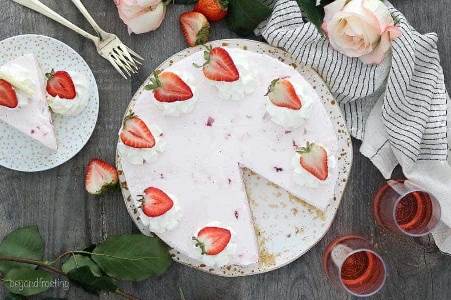 An overhead view of a gorgeous strawberry cake styles with pink roses and strawberries