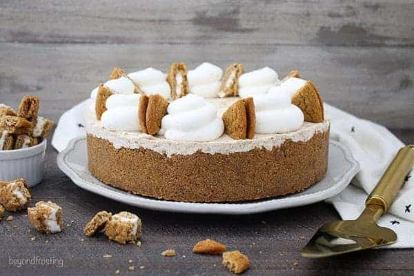 A horizontal photo of an a whole ice cream pie topped with whipped cream and oatmeal cream pies