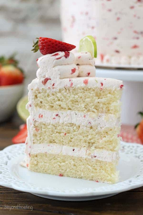 A tall slice of layer cake with a fresh strawberry frosting. Garnished with strawberries and limes