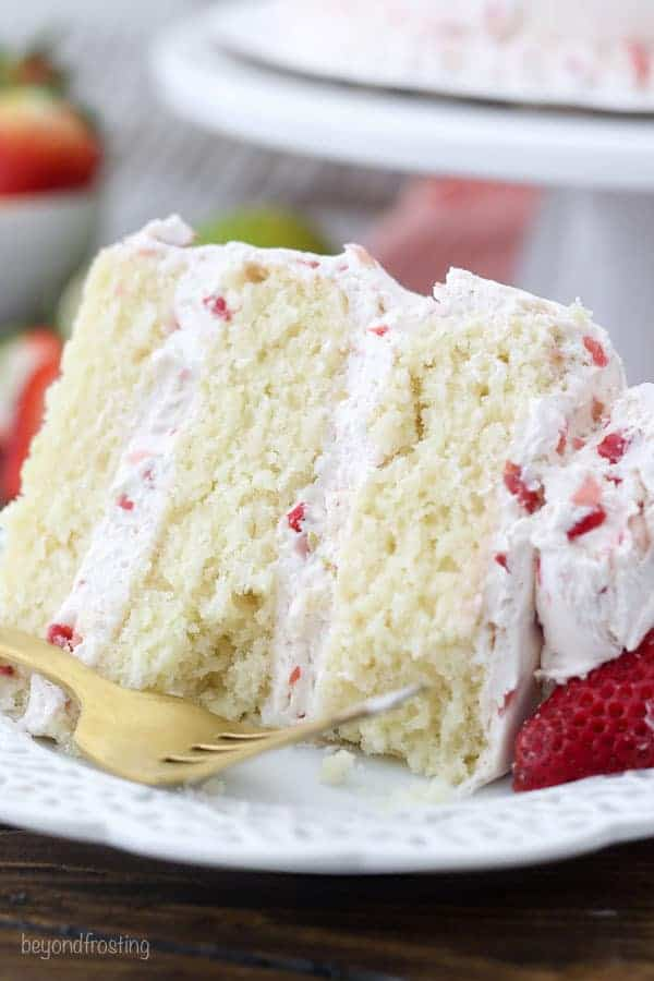 A close up on a three layer margarita cake with bites taken out of it