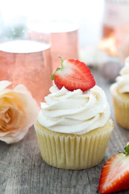 A beautiful cupcakes styled with strawberries, roses and sparkling rosé in the back.