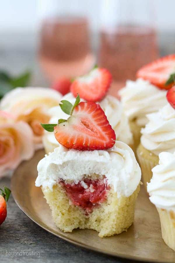 A cupcake with a bite taken out of it to show the strawberry filling