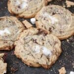 A bunch of cookies with melted marshmallow centers are laid out on a cookie sheet with a lot of crumbs and mini marshmallows