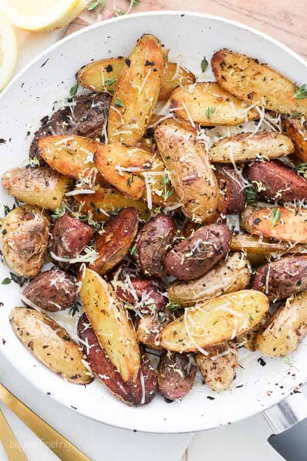 An overhead shot of a skillet with roasted lady fingerling potatoes garnished with parmesan and fresh thyme