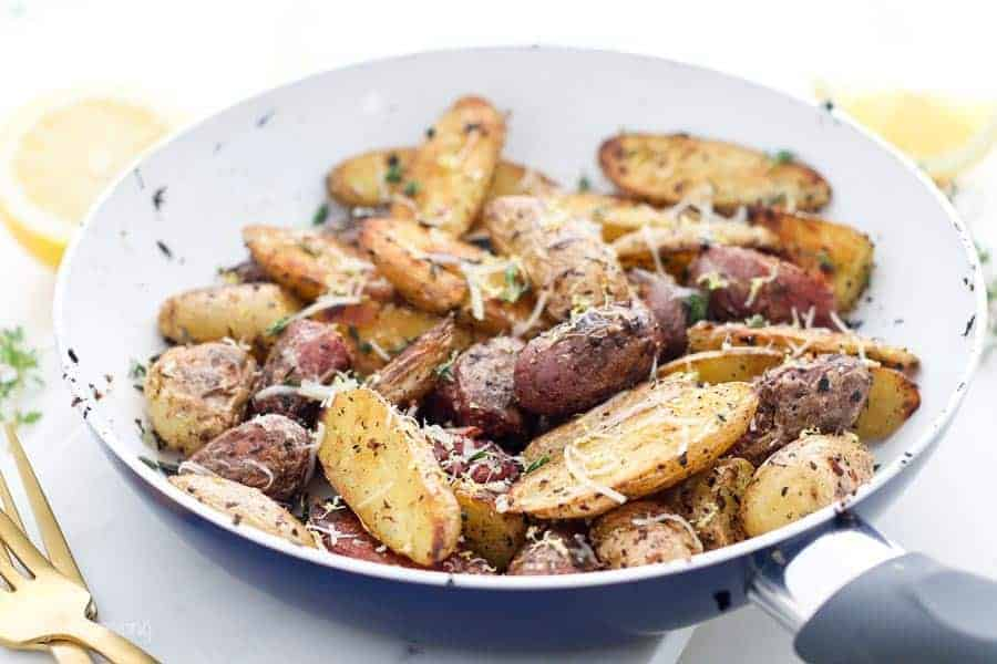A close up view of a skillet with fried crispy fingerling potatoes garnished with thyme and parmesan