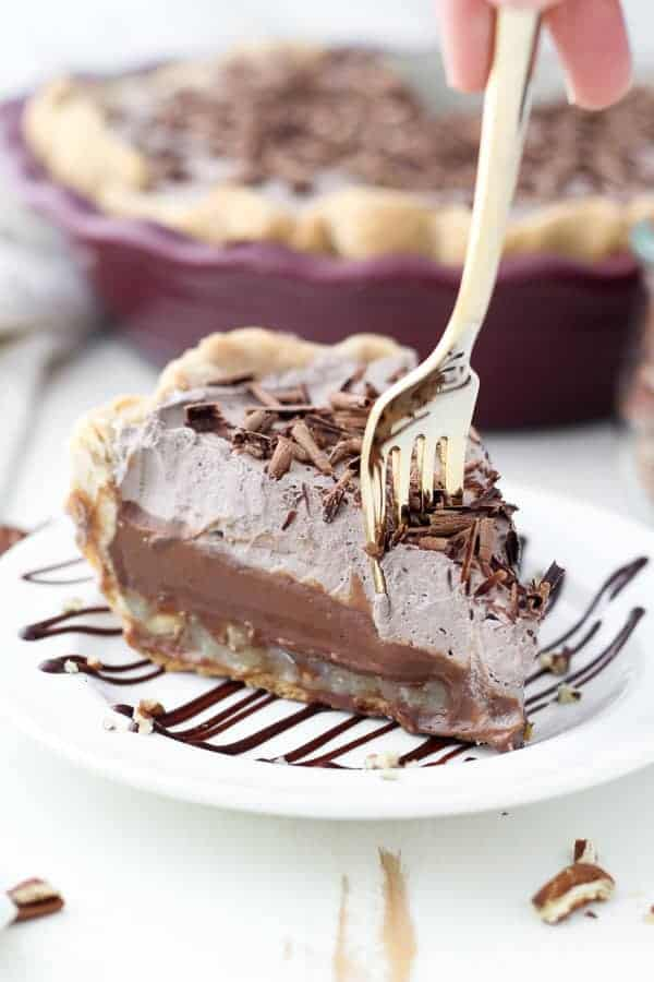 A gold fork sinking into a layered chocolate pie with pecans and coconut.
