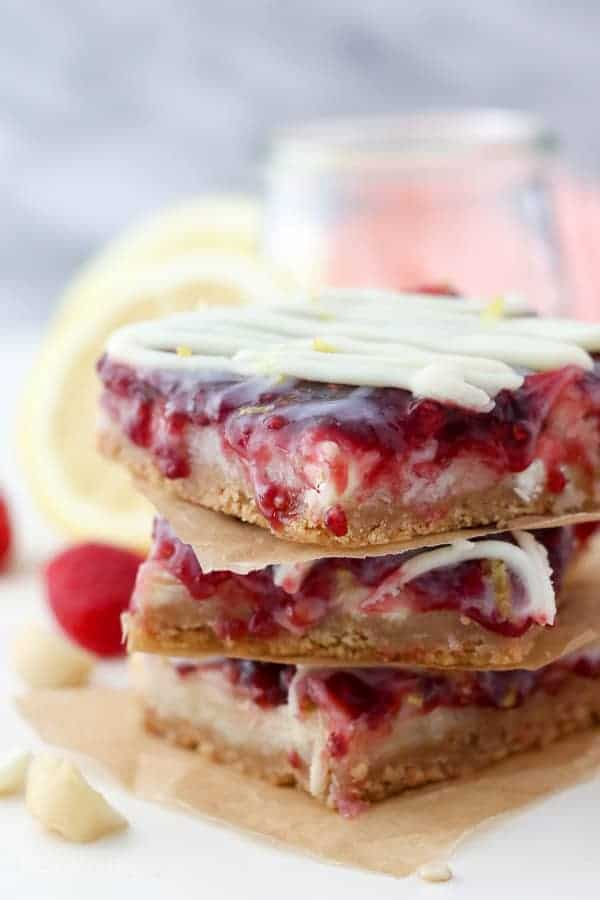 A stack of seven layer bars topped with raspberry jam, lemon zest and white chocolate