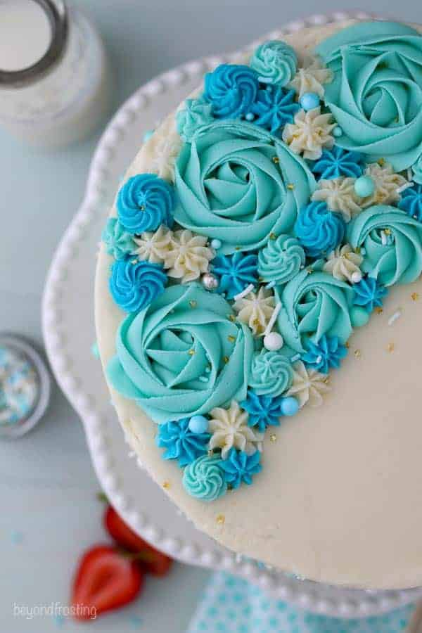 An overhead close up shot of a cake on a white cake plate. The cake is decorated with teal colored roses, blue rosettes and sprinkles.