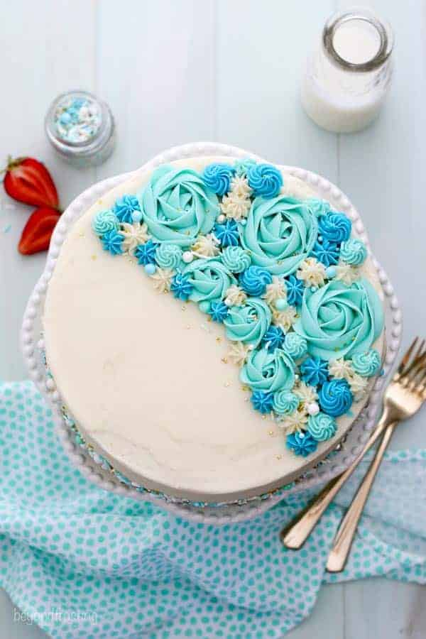 An overhead shot of a cake on a white cake plate. The cake is decorated with teal colored roses, blue rosettes and sprinkles.