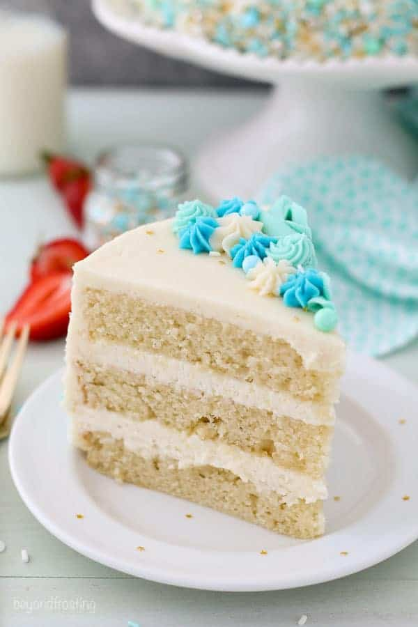 A tall slice of cake on a white plate. The cake is frosting with vanilla frosting