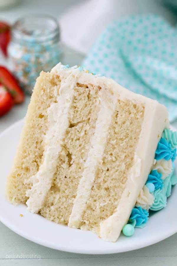 A close up shot of a slice of vanilla cake with vanilla frosting