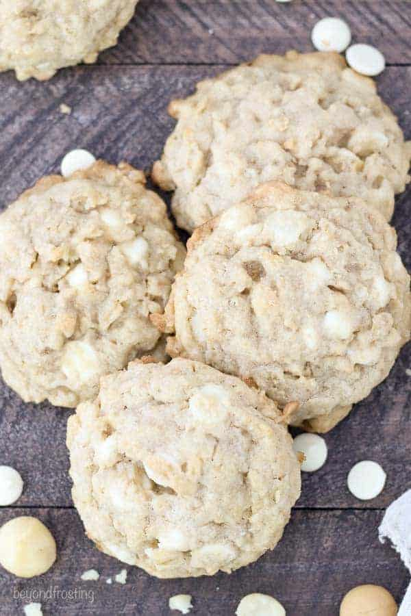 A group of 4 cookies clustered together on a wooden surface with white chocolate chips sprinkled throughout and macadamia nuts