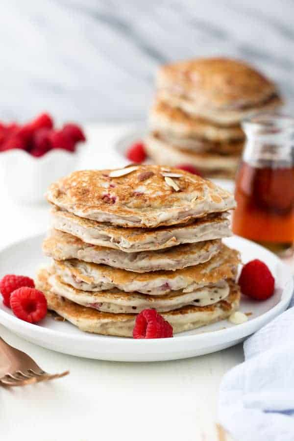 Raspberry Almond Pancakes on a white rimmed plate with fresh berries
