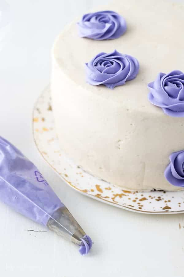 An icing bag filled with purple frosting is laying next to a cake decorated with several buttercream roses
