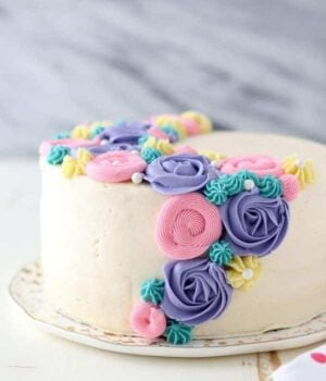 A side view of a layer cake with white frosting and colorful buttercream flowers