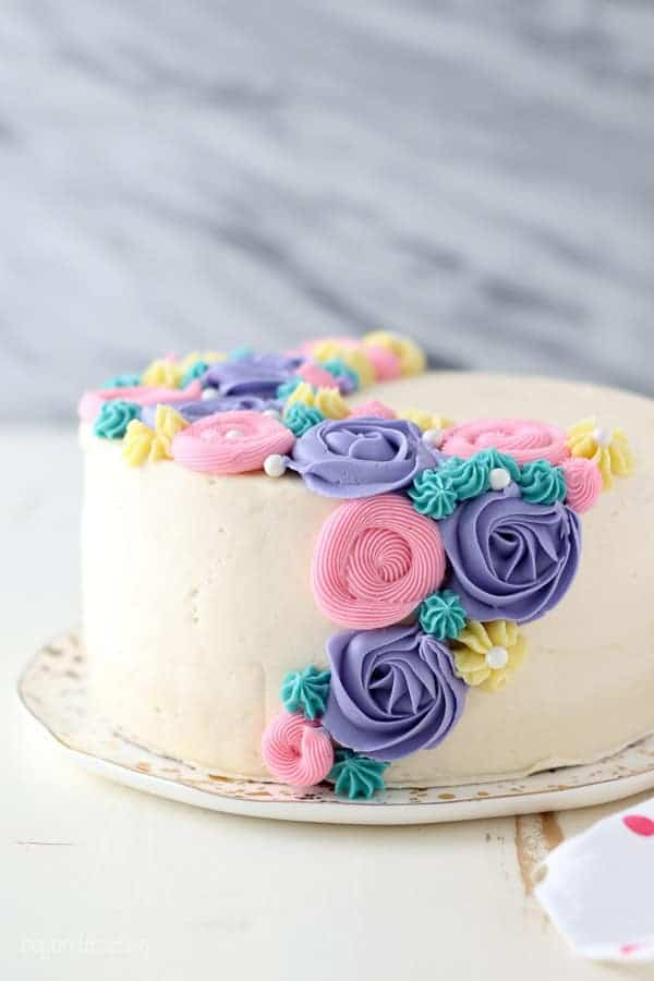 A Side View Of Layer Cake With White Frosting And Colorful Buttercream Flowers