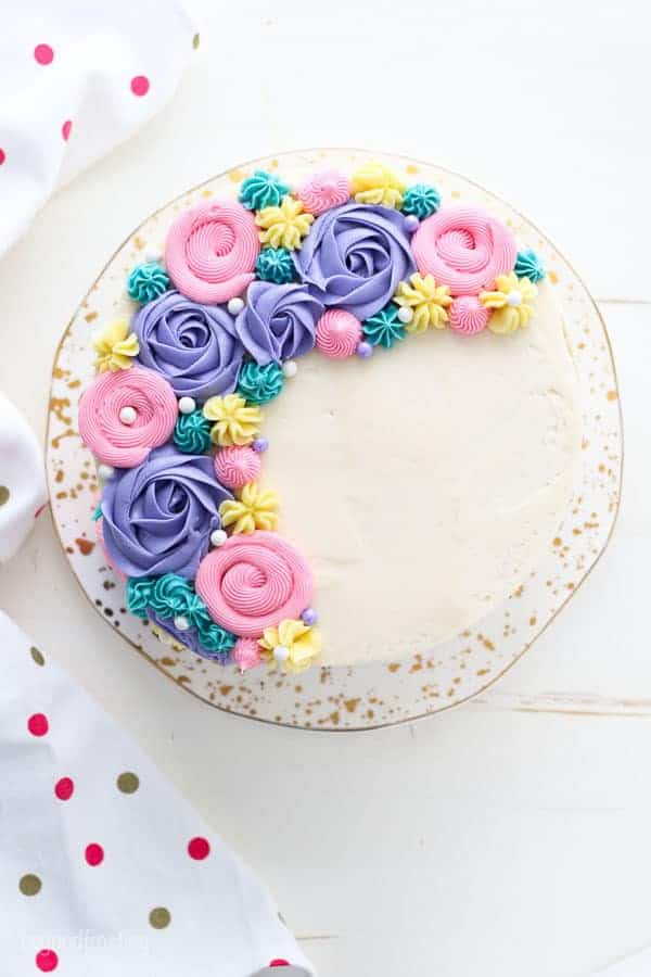 An overhead view of a beautiful cake decorated with pastel color buttercream flowers