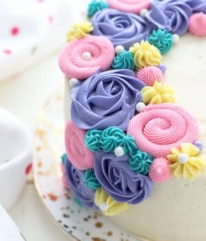 A close up view of a cake decorate with buttercream flowers and buttercream roses