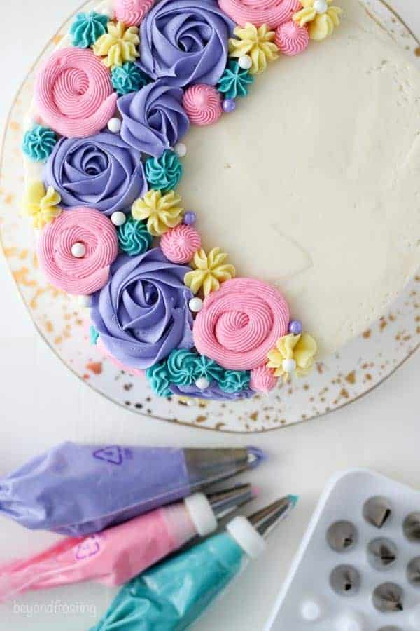A close up overhead view of a layer cake decorated with purple buttercream roses and multicolor buttercream flowers