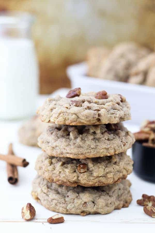 A tall stack of 4 oatmeal cookies loaded with pecans and cinnamon sticks in the background