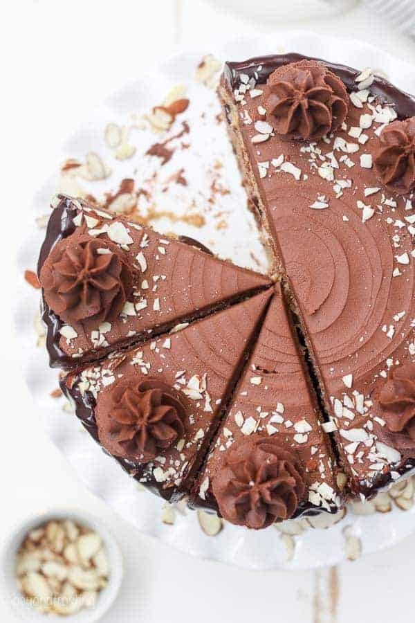 An overhead shot of a cake with one slice missing. The cake is topped with chocolate rosettes and crushed almonds