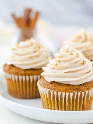 A close up shot of a pumpkin cupcake topped with a swirl of cream cheese frosting